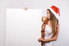 Mulher do Natal no chapéu de Santa com quadro de avisos em branco Imagem de Stock Royalty Free
