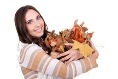 Mulher do outono que prende uma pilha das folhas Imagem de Stock