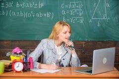 A mulher do professor senta o fundo surfando do quadro do Internet do portátil do trabalho da tabela Lição atual no uso detalhado foto de stock royalty free