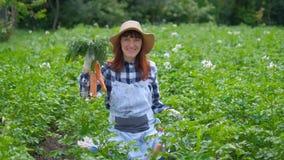 Mulher do retrato com cenouras orgânicas em um jardim vegetal filme