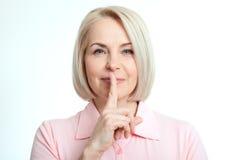 Mulher do retrato com o dedo nos bordos, ou sinal secreto da mão do gesto isolado no fundo branco Fotografia de Stock Royalty Free
