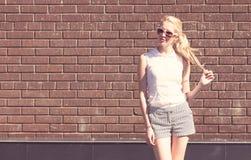 Mulher do retrato sensual exterior da forma do verão e cabelo louros novos bonitos da torção perto do fundo da parede de tijolo T Fotos de Stock Royalty Free