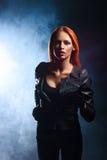 Mulher do ruivo em um jacke de couro preto imagem de stock
