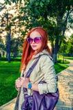 Mulher do ruivo na roupa ocasional que levanta fora em 60th óculos de sol da forma e na bolsa violeta brilhante Fotos de Stock Royalty Free