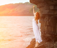 Mulher do ruivo no vestido que está na praia foto de stock royalty free