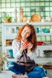 Mulher do ruivo que senta-se na pose dos lótus na loja da argila fotos de stock royalty free