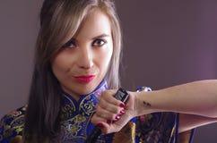 A mulher do samurai vestiu-se no vestido de seda asiático colorido tradicional do teste padrão de flor, guardando a mão na espada Foto de Stock