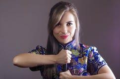 A mulher do samurai vestiu-se no vestido de seda asiático colorido tradicional do teste padrão de flor, guardando a mão na espada Fotos de Stock Royalty Free
