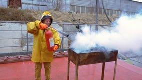 A mulher do sapador-bombeiro em uma capa de chuva amarela extingue o fogo na grade usando o extintor filme