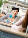 A mulher do smiley senta-se na mesa Imagem de Stock Royalty Free