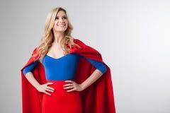 Mulher do super-herói Louro novo e bonito na imagem do superheroine no crescimento vermelho do cabo Fotografia de Stock