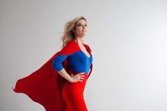 Mulher do super-herói Louro novo e bonito na imagem do superheroine no crescimento vermelho do cabo Imagem de Stock Royalty Free
