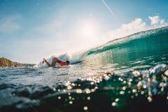 Mulher do surfista na onda do oceano e do tambor A menina da ressaca faz o pato mergulhar imagens de stock royalty free