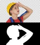 Mulher do trabalhador da constru??o do coordenador fascinada pela escala da constru??o, canal alfa fotografia de stock