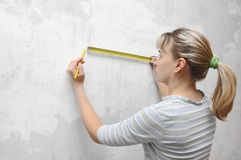Mulher do trabalhador que mede no straightedgetape da parede Foto de Stock Royalty Free