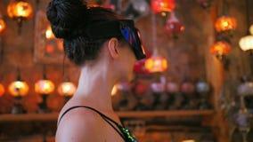 Mulher do turista com vidros de VR que compra na loja de lembrança com as lâmpadas turcas tradicionais vídeos de arquivo