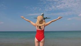 A mulher do turista no roupa de banho e no chapéu vermelhos dá boas-vindas ao avião para o curso Olá! conceito das férias filme