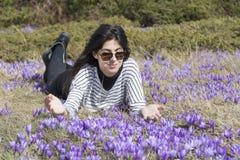 Mulher do turista que coloca em um prado com açafrões de florescência roxos Fotografia de Stock