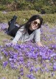 Mulher do turista que coloca em um prado com açafrões de florescência roxos Imagens de Stock