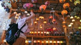 Mulher do turista que faz a foto com o smartphone na loja de lembrança com as lâmpadas turcas tradicionais video estoque