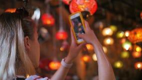 Mulher do turista que faz a foto com o smartphone na loja de lembrança com as lâmpadas turcas tradicionais vídeos de arquivo