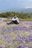 Mulher do turista que senta-se em um prado com açafrões de florescência roxos Fotos de Stock Royalty Free