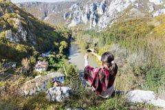 Mulher do turista que senta-se na parte superior da montanha do outono que toma fotos com o telefone fotografia de stock