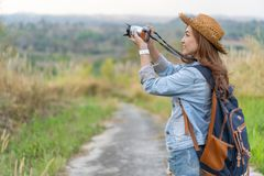 Mulher do turista que toma a foto com sua câmera na natureza foto de stock