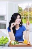 A mulher do vegetariano guarda o tomate na cozinha Fotos de Stock
