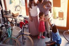 Mulher do vendedor a vender a bicicleta nova da família nova na loja foto de stock