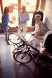 Mulher do vendedor a vender a bicicleta nova da família superior na loja imagem de stock