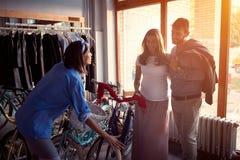Mulher do vendedor a vender a bicicleta nova dos clientes felizes na loja imagens de stock