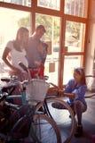 Mulher do vendedor a vender a bicicleta nova dos clientes na loja fotos de stock