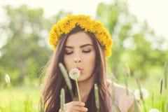 Mulher do verão que funde em flores do dente-de-leão Imagem de Stock