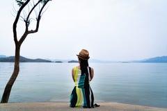 A mulher do viajante aprecia olhar o lago bonito com as montanhas no fundo imagens de stock royalty free