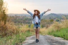 Mulher do viajante com a trouxa com os braços aumentados imagens de stock