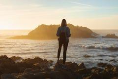 Mulher do viajante com trouxa que aprecia a vista para o mar, caminhante da menina no por do sol, conceito do curso, Califórnia,  fotos de stock royalty free