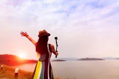 Mulher do viajante para apreciar a tomada um selfie no por do sol bonito no lago com as montanhas no fundo imagens de stock