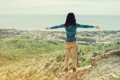 Mulher do viajante que está com os braços aumentados no pico da rocha Fotos de Stock