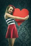A mulher do vintage no vestido vermelho abraçou o coração de papel grande Fotografia de Stock Royalty Free