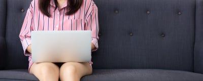 Mulher do Web site da bandeira que trabalha o portátil em linha que senta-se no sofá na sala de visitas, menina que usa o laptop  fotos de stock