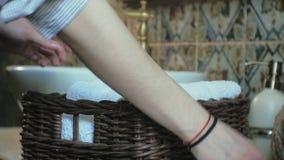 A mulher dobra toalhas macias limpas na cesta, limpando o conceito video estoque
