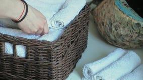 A mulher dobra toalhas macias limpas na cesta, limpando o conceito vídeos de arquivo