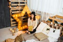 A mulher doce nova com a caixa atual no Natal decorou em casa fotografia de stock royalty free
