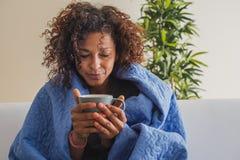 A mulher doente bebe a bebida quente durante o tempo frio fotos de stock royalty free