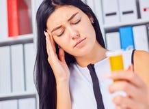 Mulher doente cansado bonita nova que senta-se no local de trabalho no escritório que guarda a garrafa com comprimidos Sentimento imagem de stock