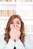 Mulher doente com frio e vírus que espirra no tecido imagens de stock