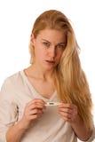 A mulher doente com a gripe e a febre que olham no termômetro isolou o ov Fotos de Stock