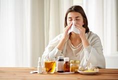 Mulher doente com o nariz de sopro da medicina a limpar imagem de stock