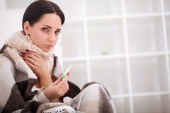 Mulher doente com termômetro flu Frio travado mulher imagem de stock